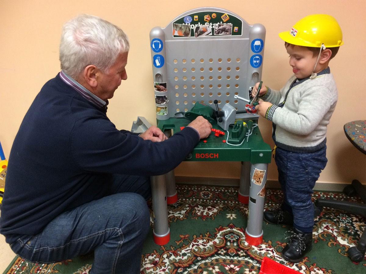 Gemeindehaus Naujiena - Enkel spielt mit Opa