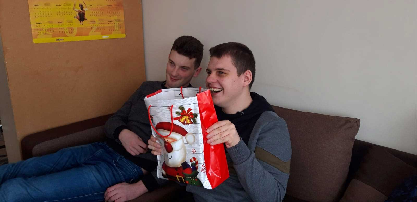 Weihnachtsfreude 2020 - zwei fröhliche Jungs auf dem Sofa beim Auspacken